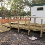 Pine decking ramp to portable toilet building
